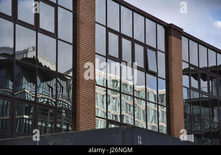 buildings reflected in glass front - Stock Photo