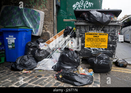 Rubbish bags left beside a bin which has a sign that reads, Persons leaving waste beside bins may receive a £50 - Stock Photo