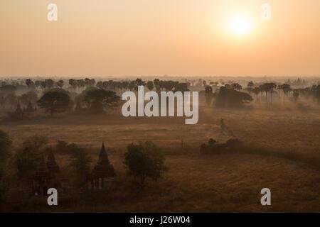 Sunrise over misty plain in Bagan, Myanmar (Burma). - Stock Photo