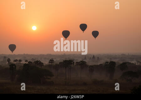 Silhouette of hot-air balloons over the plain of Bagan at sunrise in Myanmar (Burma). - Stock Photo