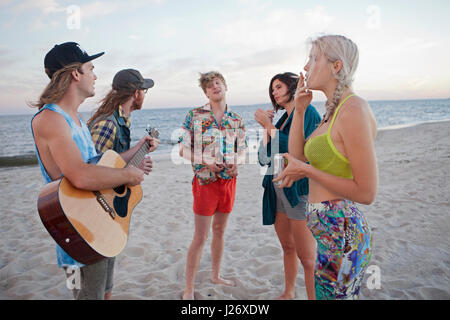 Friends playing music together on a beach - Stock Photo