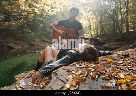 Young man serenading his girlfriend by a stream - Stock Photo