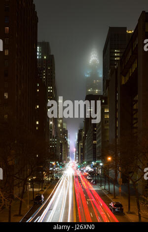 The view from Tudor City towards the Chrysler Building at night which is partially covered in low cloud, car light - Stock Photo