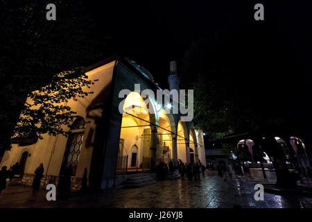 SARAJEVO, BOSNIA HERZEGOVINA - APRIL 15, 2017: People praying in front of Gazi Husrev Begova mosque in Sarajevo. - Stock Photo