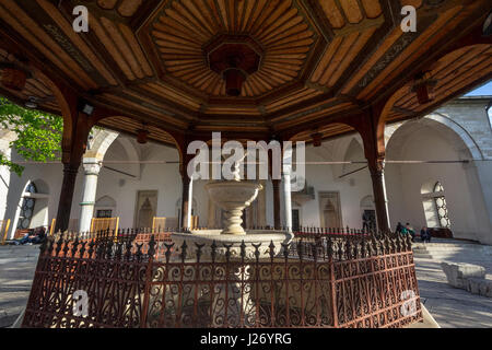 SARAJEVO, BOSNIA HERZEGOVINA - APRIL 17, 2017: Fountain of Gazi Husrev begova Mosque with people praying in the - Stock Photo