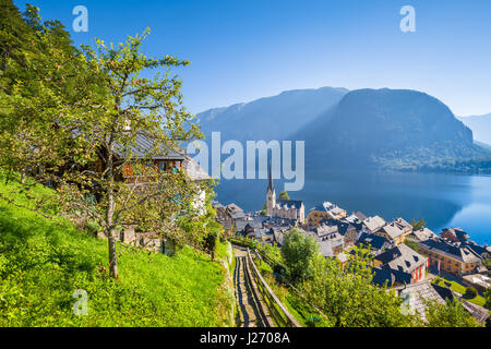 Classic postcard view of famous Hallstatt lakeside town in the Alps with idyllic pathway leading uphill on a beautiful - Stock Photo