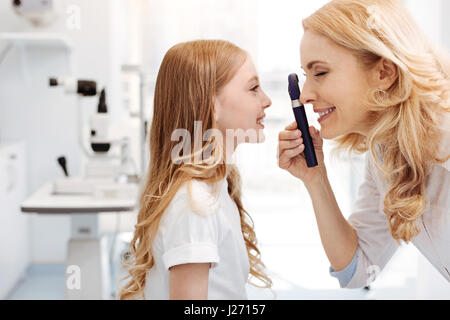 Prominent eye specialist using ophthalmoscope - Stock Photo
