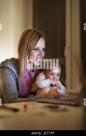 Mother with son in the arms, working on laptop - Stock Photo