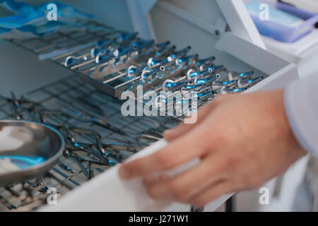 Let me choose. Professional doctor standing near medical instruments choosing the necessary one while going to work - Stock Photo