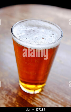 glass of pale ale beer on pub table - Stock Photo