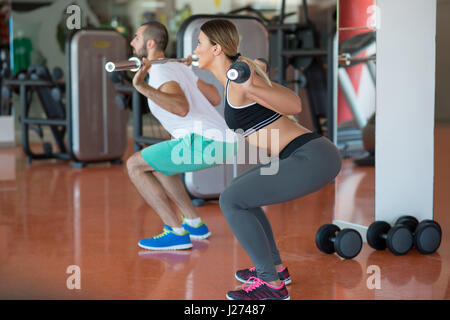 young man and woman with barbell flexing muscles and making shoulder press squat in gym - Stock Photo