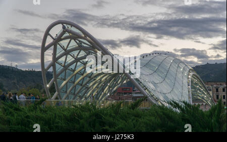 TBILISI, GEORGIA-SEP 25, 2016: New glass bridge across Kura river. Symbol of peace - Stock Photo