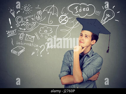 Young handsome man with graduation hat looking up thinking about education has many ideas about future life isolated - Stock Photo
