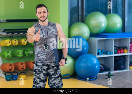 Portrait of a muscular trainer showing thumbs up. - Stock Photo