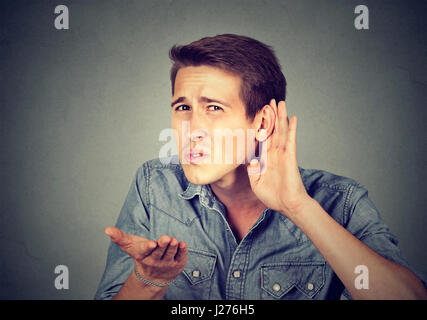 hard of hearing man placing hand on ear asking someone to speak up or listening to bad news, isolated on gray background. - Stock Photo
