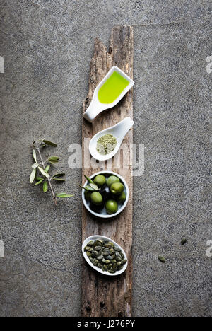 Green food: olive oil, macha tea, olives, pumpkin seed on grey background - Stock Photo