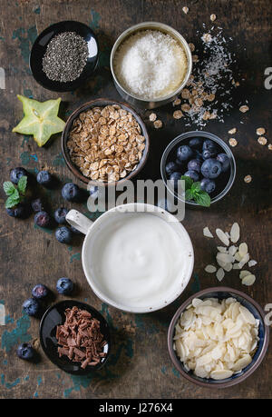 Ingredients for making smoothie for healthy breakfast. Bowls of yogurt, blueberries, granola, almond chia seeds, - Stock Photo