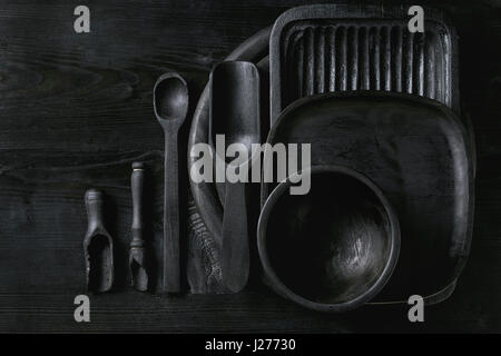 Black burnt wooden empty kitchenware cutting board, plates, scoop and spoon over black wood background. Flat lay - Stock Photo