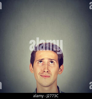 Portrait closeup funny confused skeptical man thinking looking up isolated on gray wall background with copy space - Stock Photo