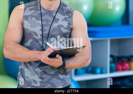 Portrait of a muscular trainer writing on clipboard - Stock Photo