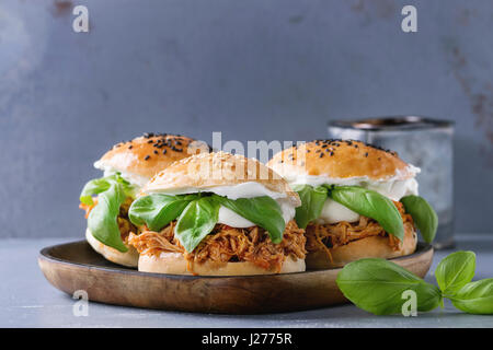 Homemade mini burgers with pulled chicken, basil, mozzarella cheese and yogurt sauce on wooden plate over gray texture - Stock Photo