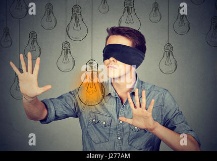 Blindfolded young man walking through light bulbs searching for bright idea - Stock Photo