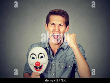 Portrait young upset angry screaming man holding a clown mask expressing cheerfulness happiness isolated on gray - Stock Photo