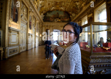 Young woman tourist is visiting the Apollo Gallery at the Louvre museum in Paris, France. - Stock Photo