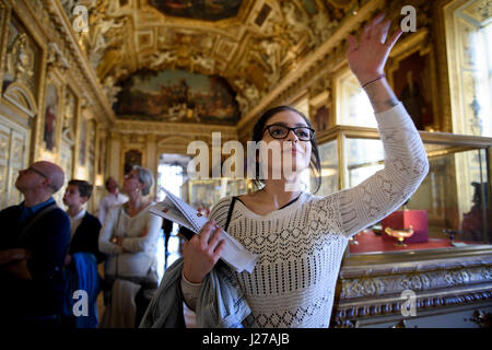 Young woman is waving inside the Apollo Gallery at the Louvre museum in Paris, France. - Stock Photo