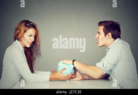 Finances in divorce concept. Wife and husband can not make settlement holding piggy bank sitting at table looking - Stock Photo