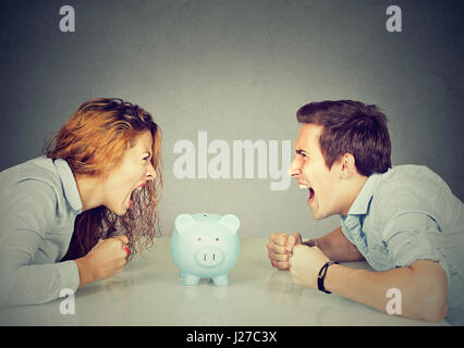 Finances in divorce concept. Wife and husband can not make settlement screaming piggy bank in-between sitting at - Stock Photo