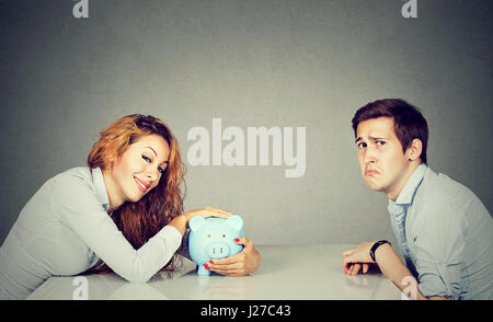 Finances in divorce concept. Happy wife with piggy bank sitting across the table from sad desperate ex husband - Stock Photo