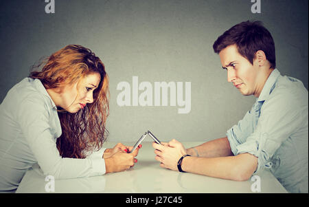 Smartphone addiction concept. Frustrated annoyed young woman and man sitting at table with smartphone and do not - Stock Photo