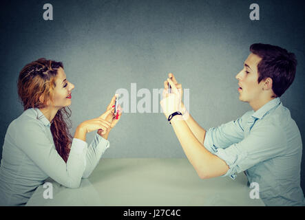 Young man and woman sitting at table using mobile phones, texting via social networks with obsessed expression or - Stock Photo