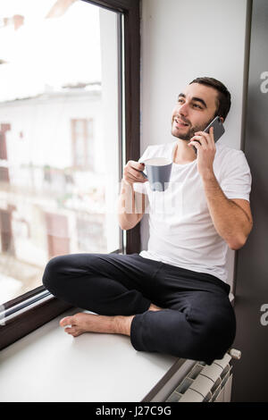 Handsome man sitting on windowsill and calling on phone - Stock Photo