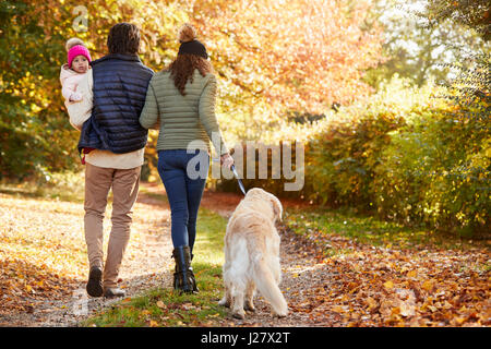 Family With Daughter And Dog Enjoy Autumn Countryside Walk - Stock Photo