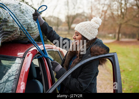 Young woman tying Christmas tree to roof of a car, side view - Stock Photo