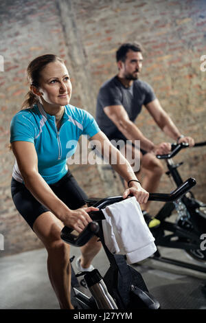 Sporty fit couple in sports clothing doing training on bicycle - Stock Photo