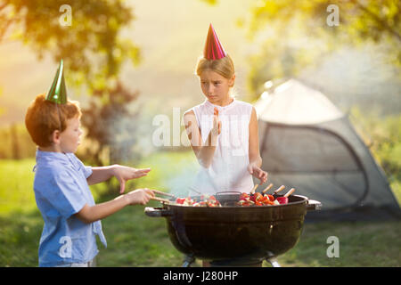 children having a barbecue party on camping - Stock Photo