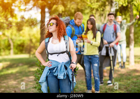 Young hiker woman with group of hikers in woods as hobby on a mission - Stock Photo