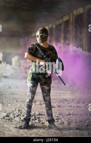female paintball player in dramatic scene - Stock Photo