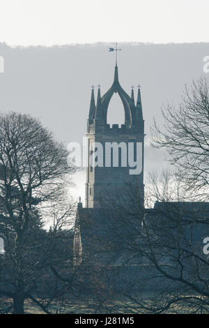 Scots Crown spire of All Hallows Church, Tillington, Sussex, December. Low mist in front of South Downs. Morning. - Stock Photo