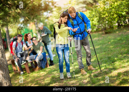 Girl and boy on break from walking in woods look at map - Stock Photo
