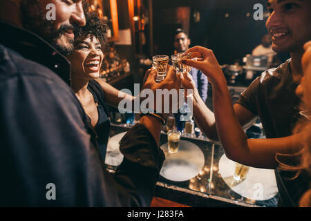 Friends toasting each other with shots of vodka as they enjoy a relaxing night out together at the pub. Group of - Stock Photo
