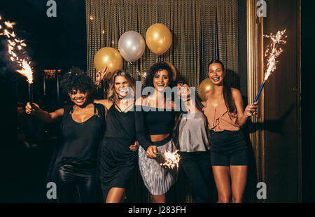 Shot of group of girls celebrating new years eve at the nightclub. Group of female friends partying in pub with - Stock Photo