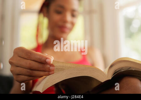 Happy female student reading book and sitting on sofa. Young african american woman relaxing, black girl lying on - Stock Photo