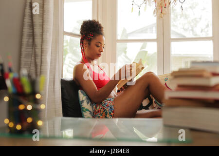 Happy female student reading book and sitting on sofa. Young african american woman relaxing, black girl lying on couch. Hispanic people and lifestyle