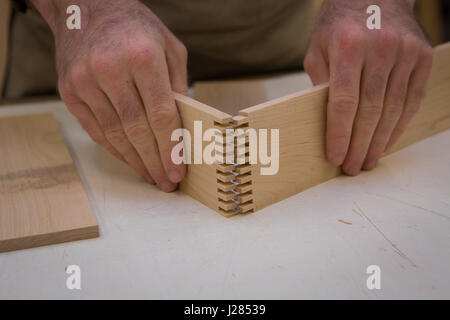 Midsection of carpenter joining wooden planks at table in workshop - Stock Photo
