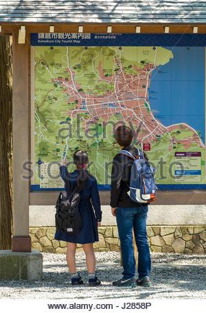 Man and woman looking at large map of Kamakura, Kōtoku-in Buddhist temple, Kamakura, Kanagawa Prefecture, Honshu, - Stock Photo