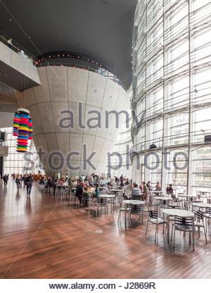 People sitting at tables inside of The National Art Center art museum designed by Kisho Kurokawa, Minato, Tokyo, - Stock Photo